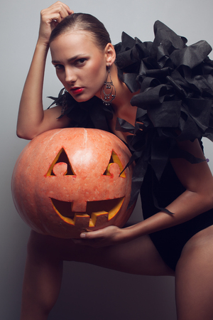 Fashionable model posing with halloween pumpkin photo