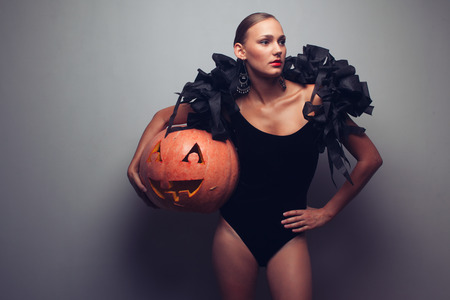 Fashionable female model holding halloweens pumpkin. Studio shot Reklamní fotografie