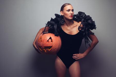 Modieuze vrouwelijke model bedrijf halloweens pompoen. Studio-opname