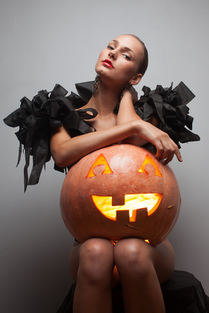 Closeup shot of fashionable model in exclusive black dress sitting with pumpkin photo