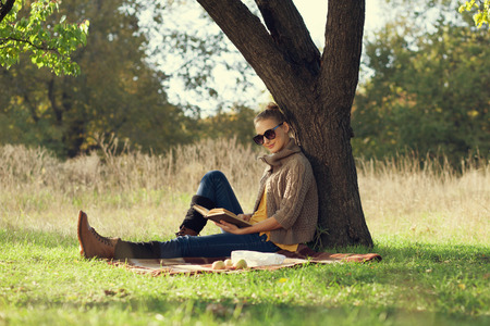 Hipster style young woman reading a book in autumn park during picknic