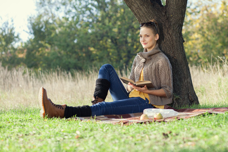 under tree: Young woman have rest with book under the tree during picnic