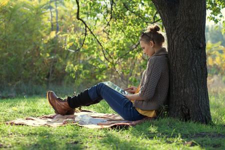 Hipster girl leaning on a tree and using tablet computer Reklamní fotografie