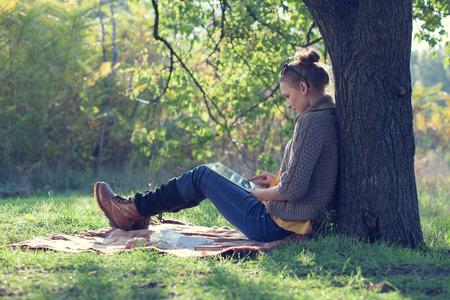 나무 아래에서 휴식하는 동안 태블릿 PC를 사용 소식통 스타일의 젊은 여성