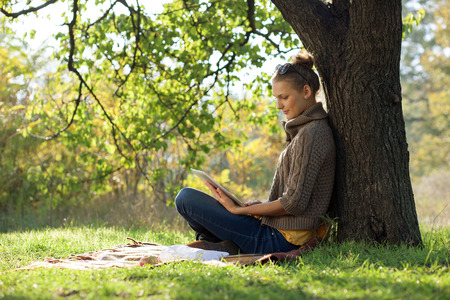 Distance education. Young woman sitting near from tree and working with ipad.