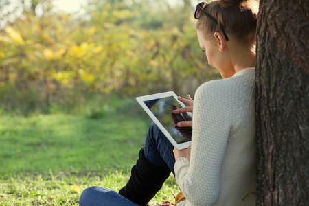 Colorful Close Up of using ipad young woman in the park. Touching touchscreen photo
