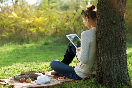 遠隔教育。屋外の散歩中に ipad を使用して座っている女性