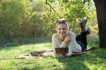 Lachende vrouw met behulp van computer in openlucht Stockfoto
