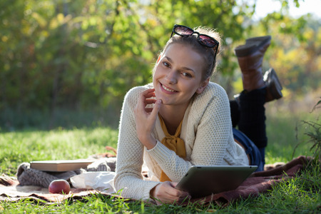 smiling woman lying on bedding with ipad during fun outdoors photo