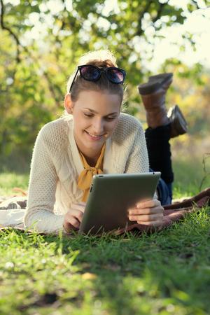 Detailní záběr na šťastné ženy pomocí počítače tablet venku