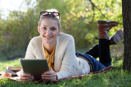 smiling teen girl lying with tablet pc under the tree in evening sunlight outdoors photo