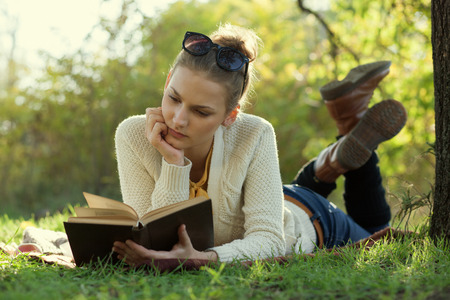 Close Up portrait of reading trendy girl with book lying beneath a tree in the evening photo