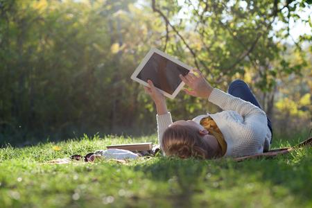 공원에서 picknic 동안 태블릿 PC와 녹색 잔디에 침대에 누워 여자