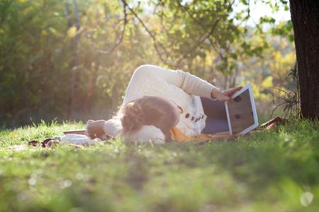 Liggende vrouw kijken in ipad scherm tijdens rust in het park in de avond