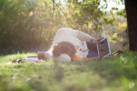 Lying woman watching in touchpad screen during rest in the park in evening