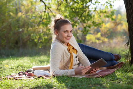 woman lying on bedding on green grass with ipad during rest in the park photo