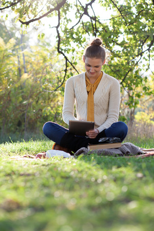 woman sitting on bedding on green grass with ipad during picknic in the park