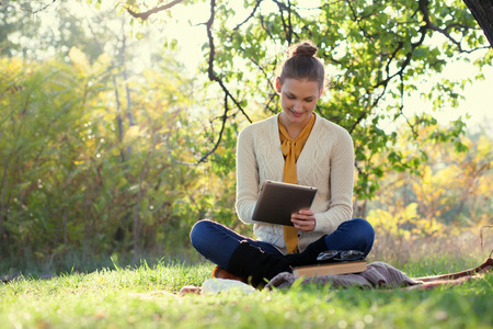 Sitting woman using tablet pc during fun outdoors