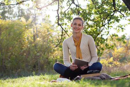 picknic: woman sitting on bedding on green grass with tablet pc during picknic in the park