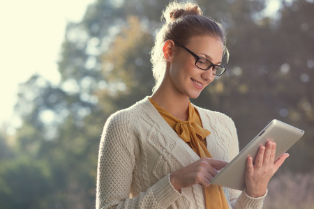 closeup of happy woman in glasses using tablet pc in the park