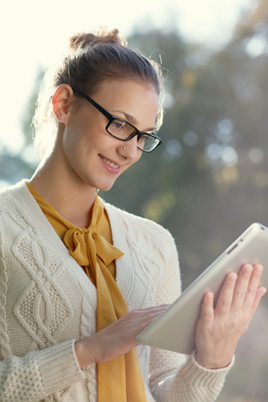 Closeup of young smart woman with ipad outdoors  Distance education  photo
