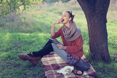 Young trendy woman eating apple and using tablet computer during picnic photo
