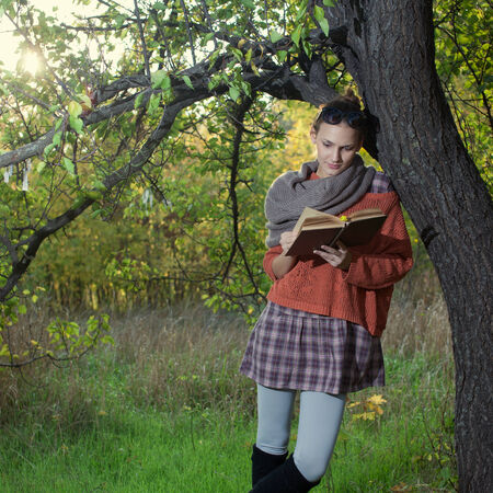 Hipster girl reading a book leaning on a tree photo