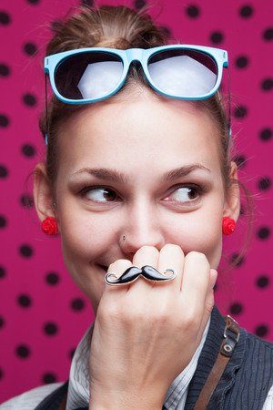 Closeup of smiling trendy girl showing mustache on pink background Reklamní fotografie