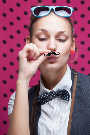 funny face of hipster style girl posing with mustache photo