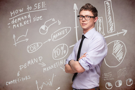 smiling man in glasses near blackboard with economic graphs Stock Photo