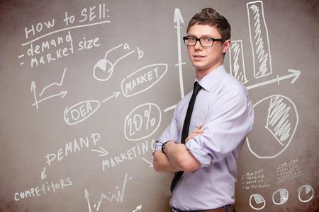 smiling man in glasses near blackboard with economic graphs Archivio Fotografico