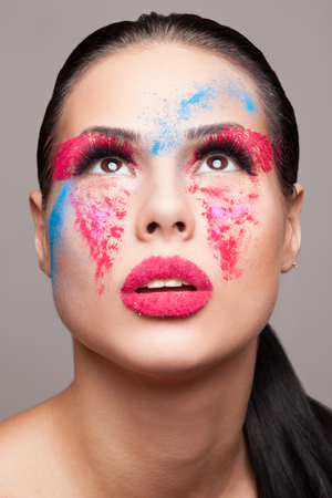 dry powder: Beauty shot of fashionable women face with pink, red and blue dry powder  red glitters on lips  FaceArt Stock Photo