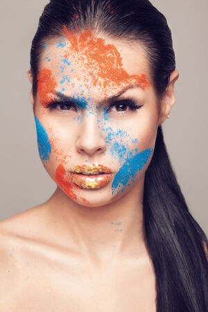 faceart: Beauty shot of emotional female face with orange and blue dry powders  gold glitters on lips  FaceArt