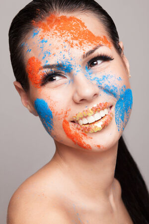 faceart: Beauty shot of smiling model face with orange and blue dry colours  gold glitters on lips  FaceArt Stock Photo