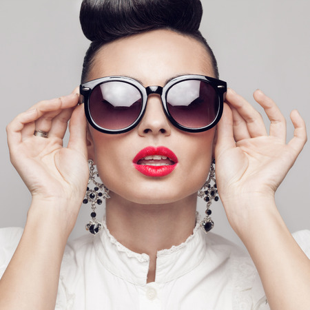Close Up portrait of beautiful vintage styling model wearing round black sunglasses. Updo, large earrings photo