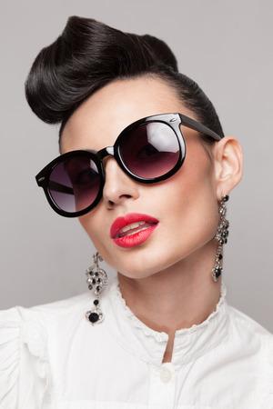라운드 검은 색 선글라스를 착용하는 아름 다운 빈티지 스타일 모델의 초상화를 닫습니다. 를 updo, 큰 귀걸이