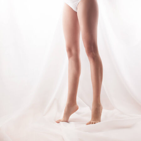 varicose veins: Womans legs standing on tiptoe. high key