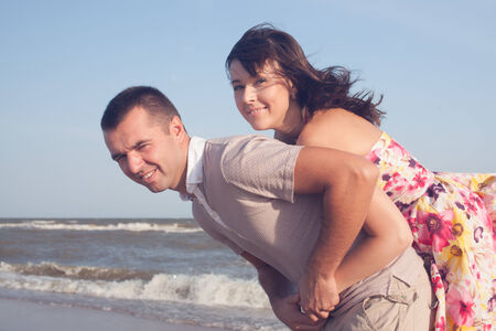 carrying girlfriend: Portrait of man carrying girlfriend on his back