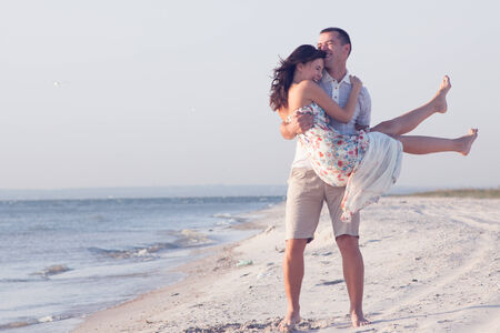 Verry happy couple enjoy each other during sunset on the beach. Man holding woman on hands