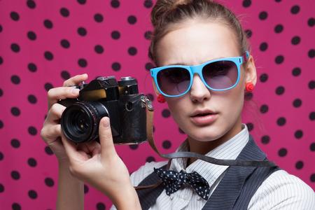 Close-up van trendy meisje gezicht in kleurrijke zonnebril met uitstekende camera Stockfoto