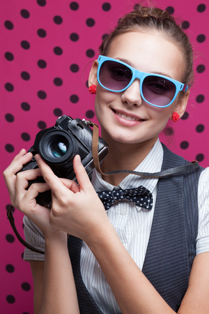 Smiling hipster girl with vintage camera  Trendy teenager in checkered red shirt and bow-tie and sunglasses