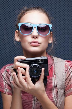 Trendy dívka v brýlích hraje opice s kamerou. Duck Face. Našpulené rty
