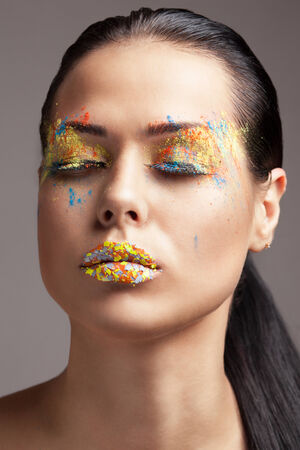 faceart: Beauty shot of face with Orange, yellow and grey glitters. FaceArt