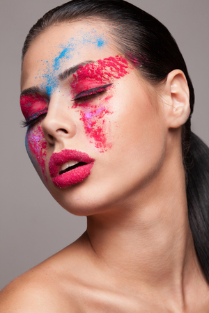 faceart: Beauty shot of fashionable women face with pink, red and blue dry colours. red glitters on lips. FaceArt