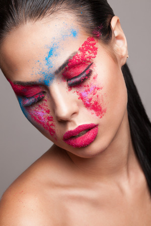 dry powder: Beauty shot of fashionable womans face with pink, red and blue dry powder. red glitters on lips. FaceArt Stock Photo