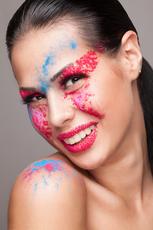 faceart: Beauty shot of smiling face with pink, red and blue dry powders. red glitters on lips. FaceArt Stock Photo