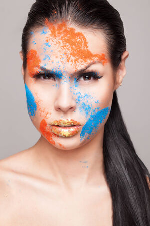 faceart: Beauty shot of emotional female face with orange and blue dry powders. gold glitters on lips. FaceArt