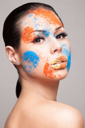 faceart: Beauty shot of woman`s face with orange and blue dry powders. gold glitters on lips. FaceArt