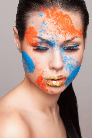 faceart: Beauty shot of posing model face with orange and blue dry colours. gold glitters on lips. FaceArt Stock Photo