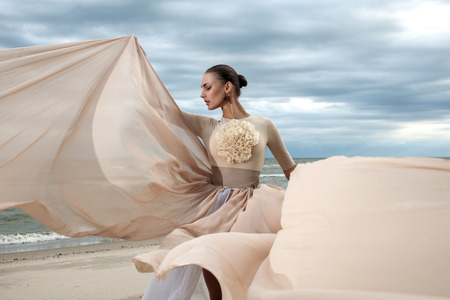 Close-up portret van het model gezicht tijdens poseren met lange jurk op het strand